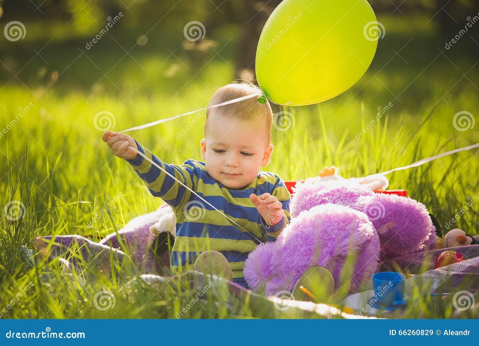 Petit bébé garçon jouant des jouets se reposant sur la longue herbe verte dehors