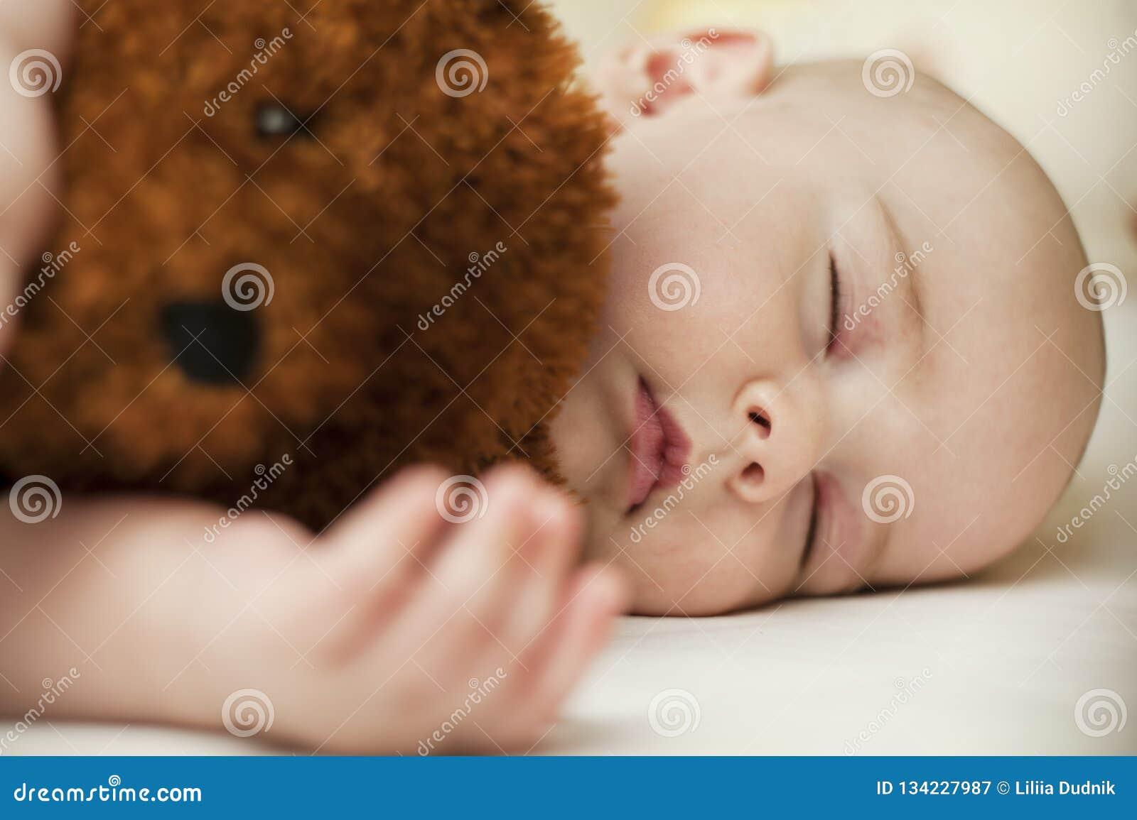 Petit bébé mignon dormant dans un sommeil doux étreignant un ours