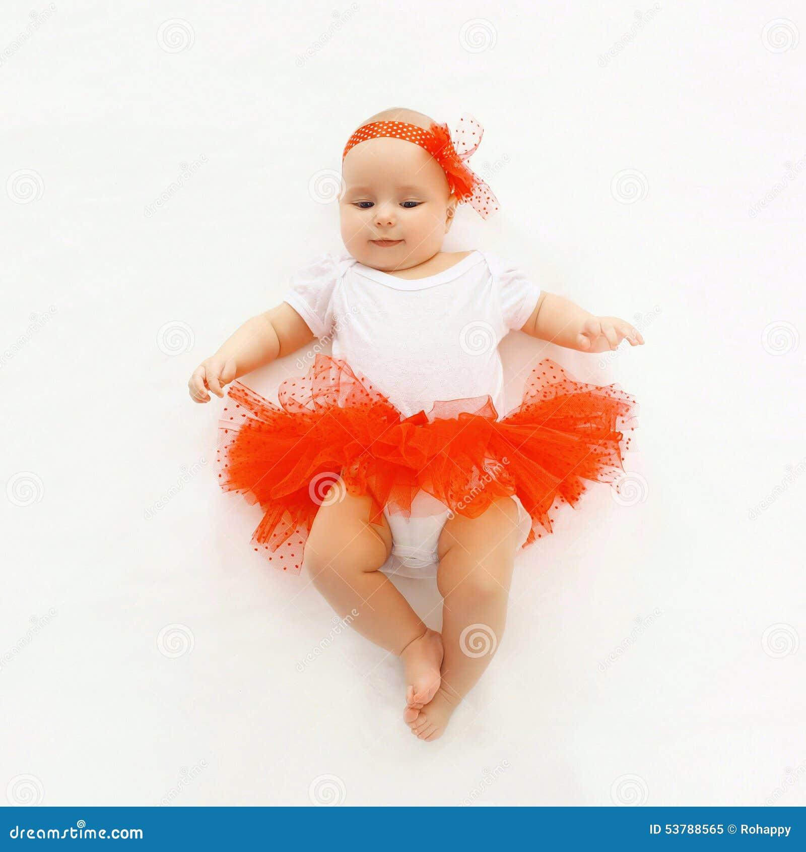 Petit bébé mignon se situant dans la jupe rouge