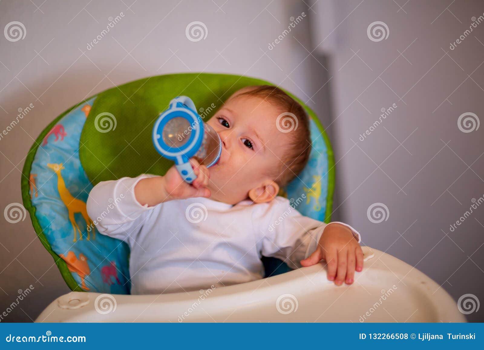Petit bébé s asseyant dans la chaise pour l alimentation et l eau potable avec