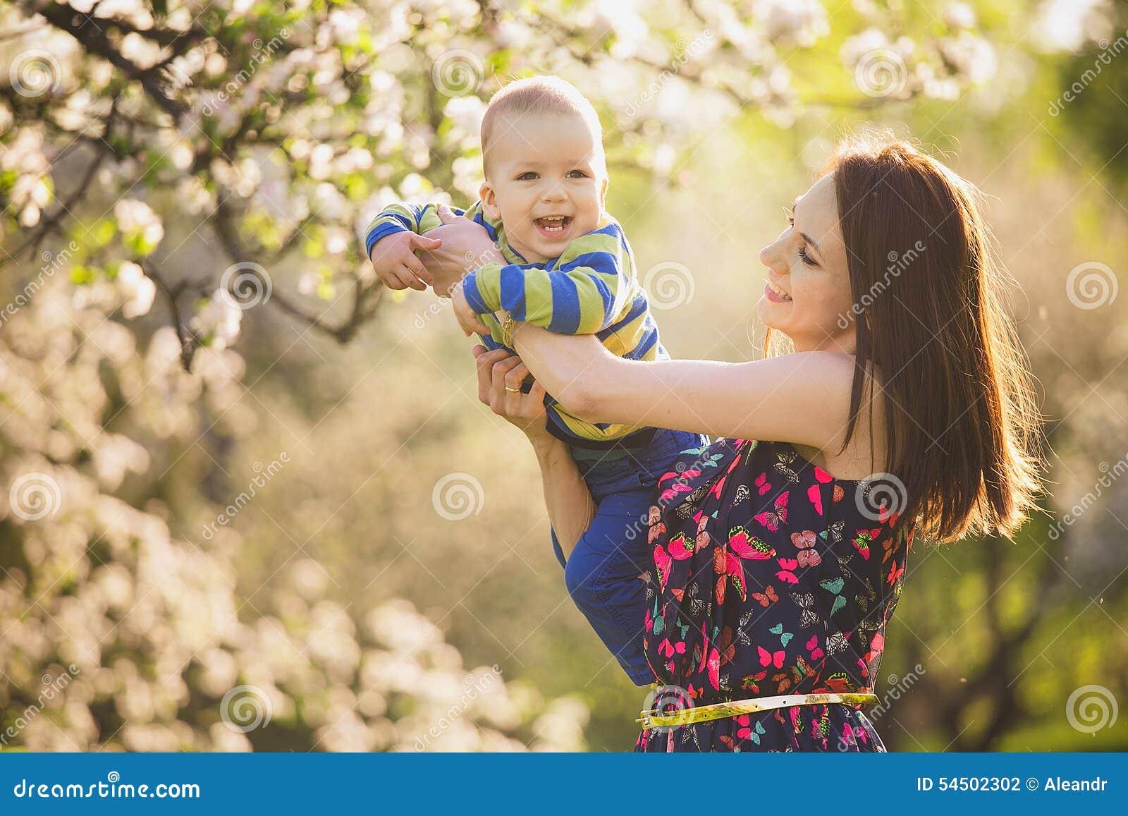 Petit bébé sur des mains de mère femme jouant avec l enfant dehors