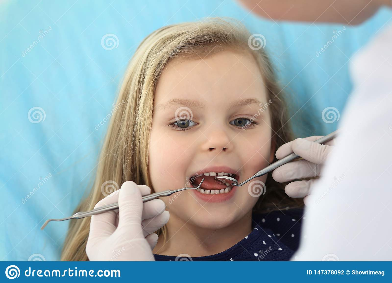 Petit b?b? s asseyant ? la chaise dentaire avec la bouche ouverte et crainte se sentante pendant le contr?le oral vers le haut du