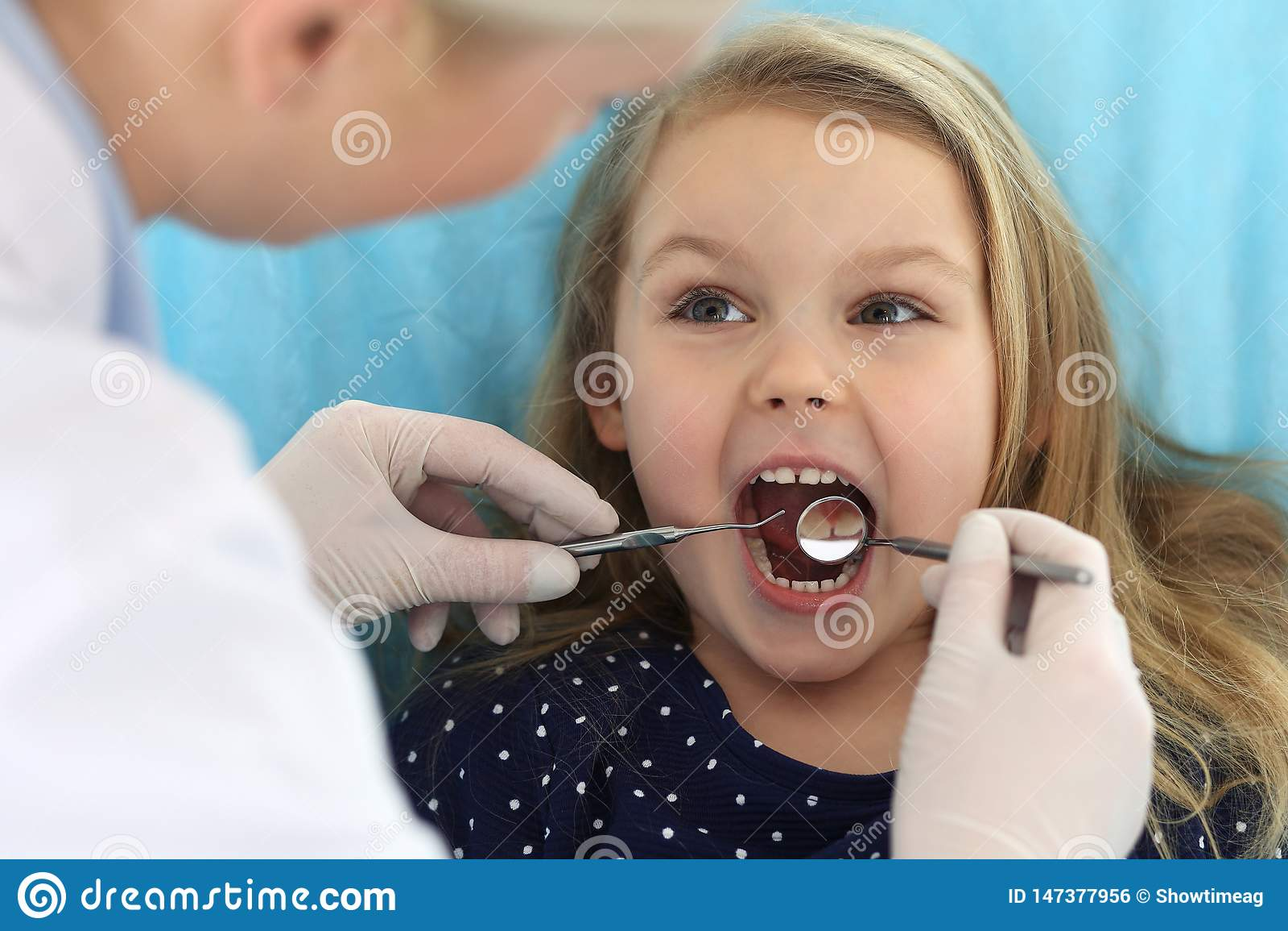 Petit b?b? s asseyant ? la chaise dentaire avec la bouche ouverte pendant le contr?le oral vers le haut de tandis que docteur Bur