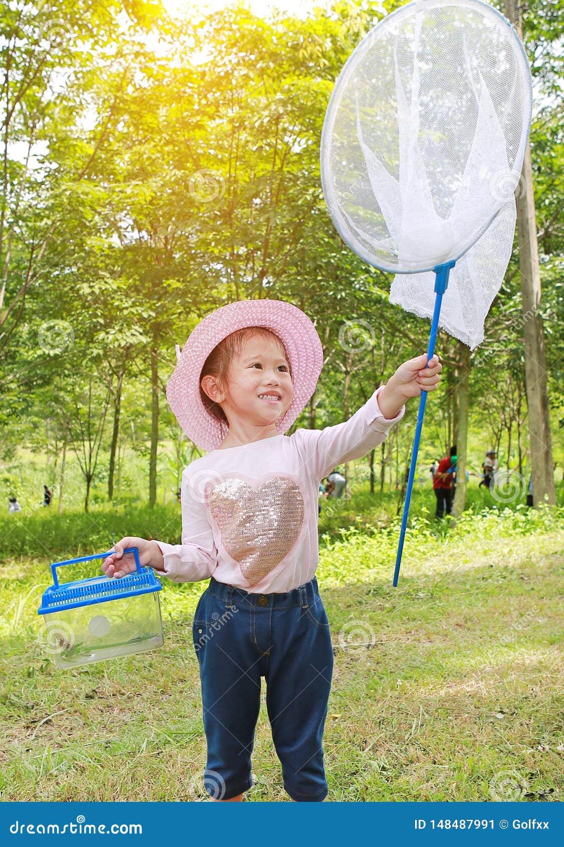 Petit chapeau de paille asiatique adorable d usage de fille dans un domaine avec le filet d insecte en été Activit? en plein air