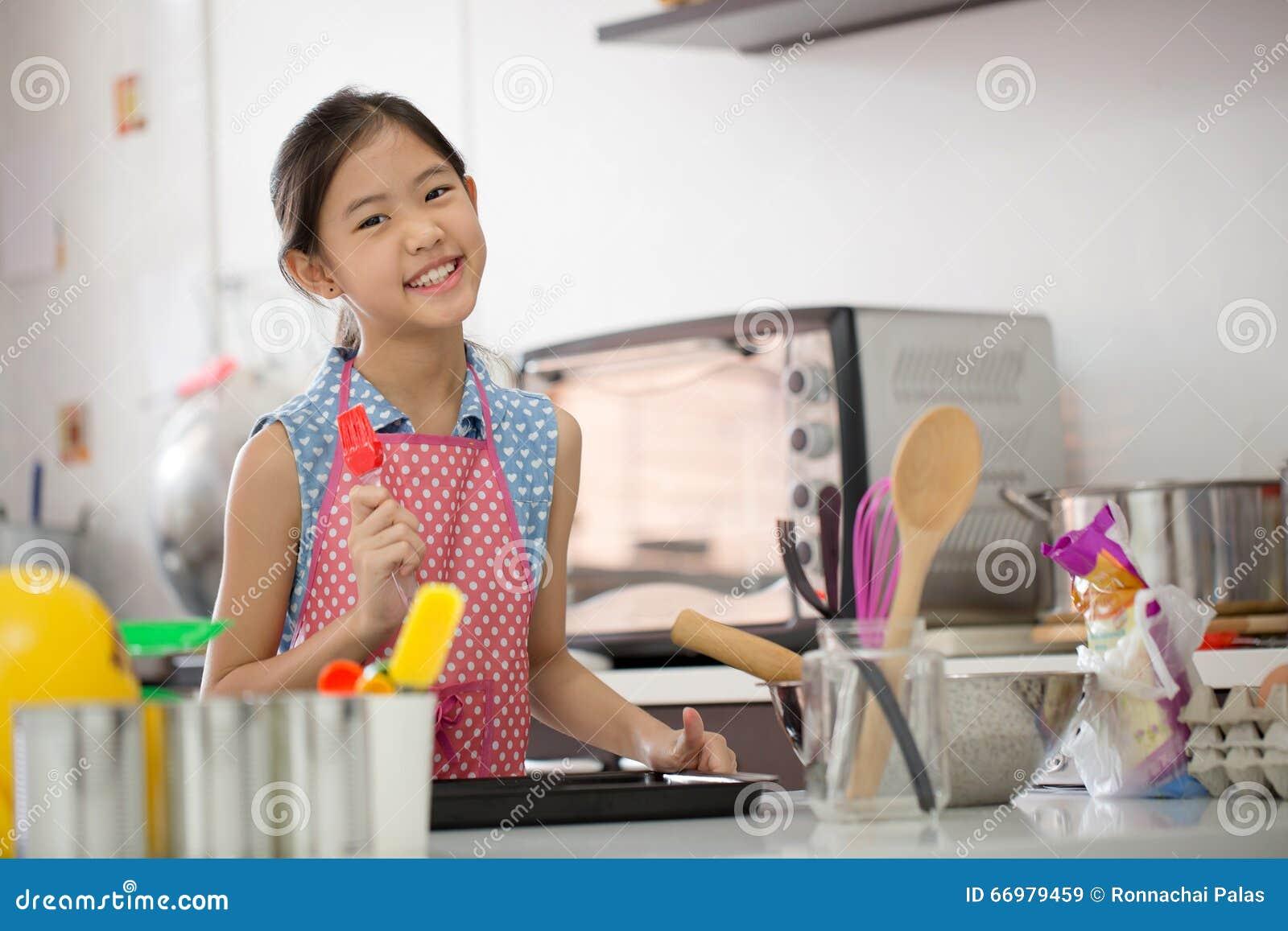 Petit chef mignon asiatique faisant cuire une boulangerie dans la cuisine