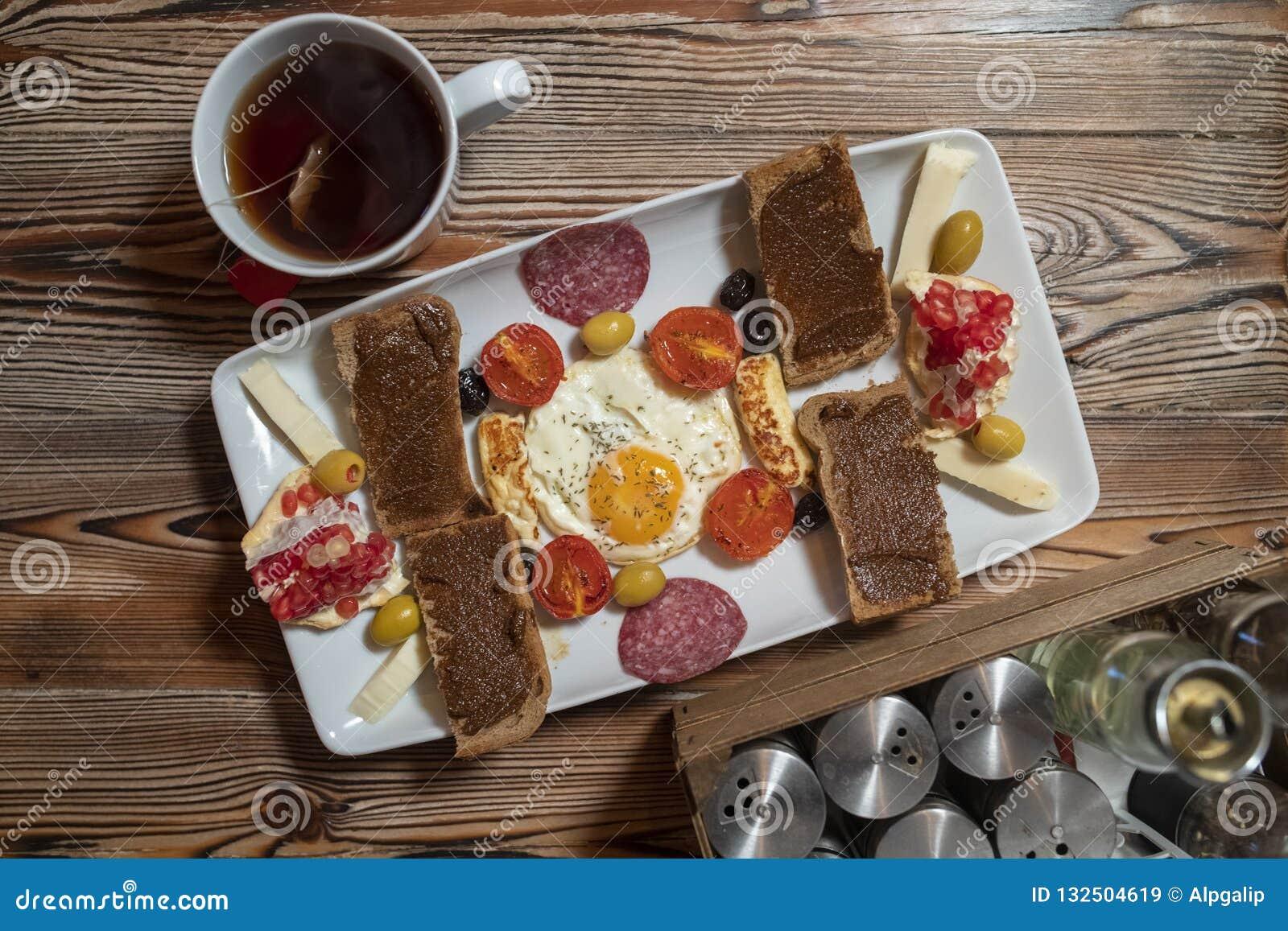 Petit déjeuner avec l oeuf au plat, le pain de seigle, la grenade, la pâte de caroube, les fromages, les olives, le salami sec, l