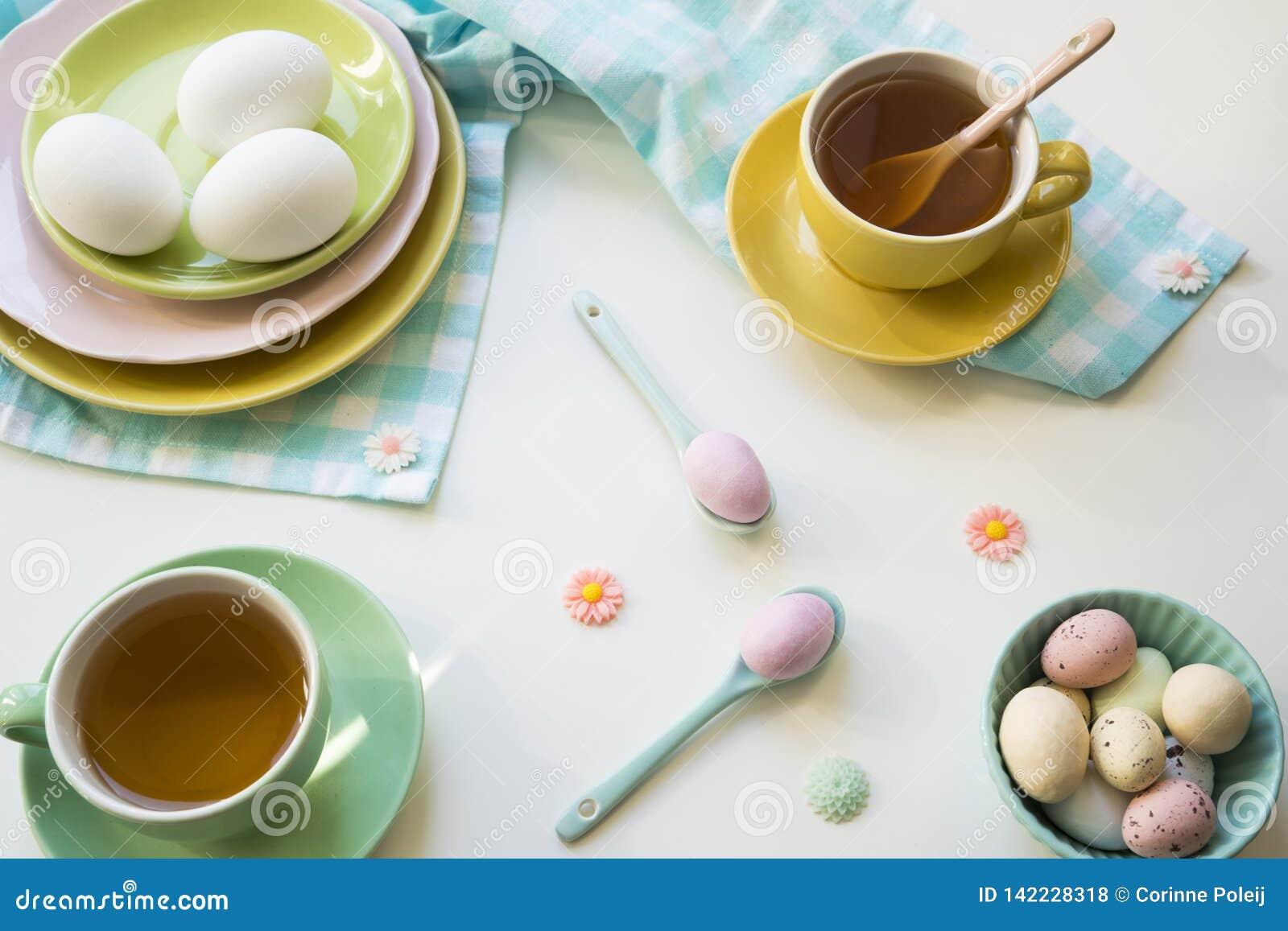 Petit déjeuner avec les oeufs et le thé de pâques dans des couleurs lumineuses