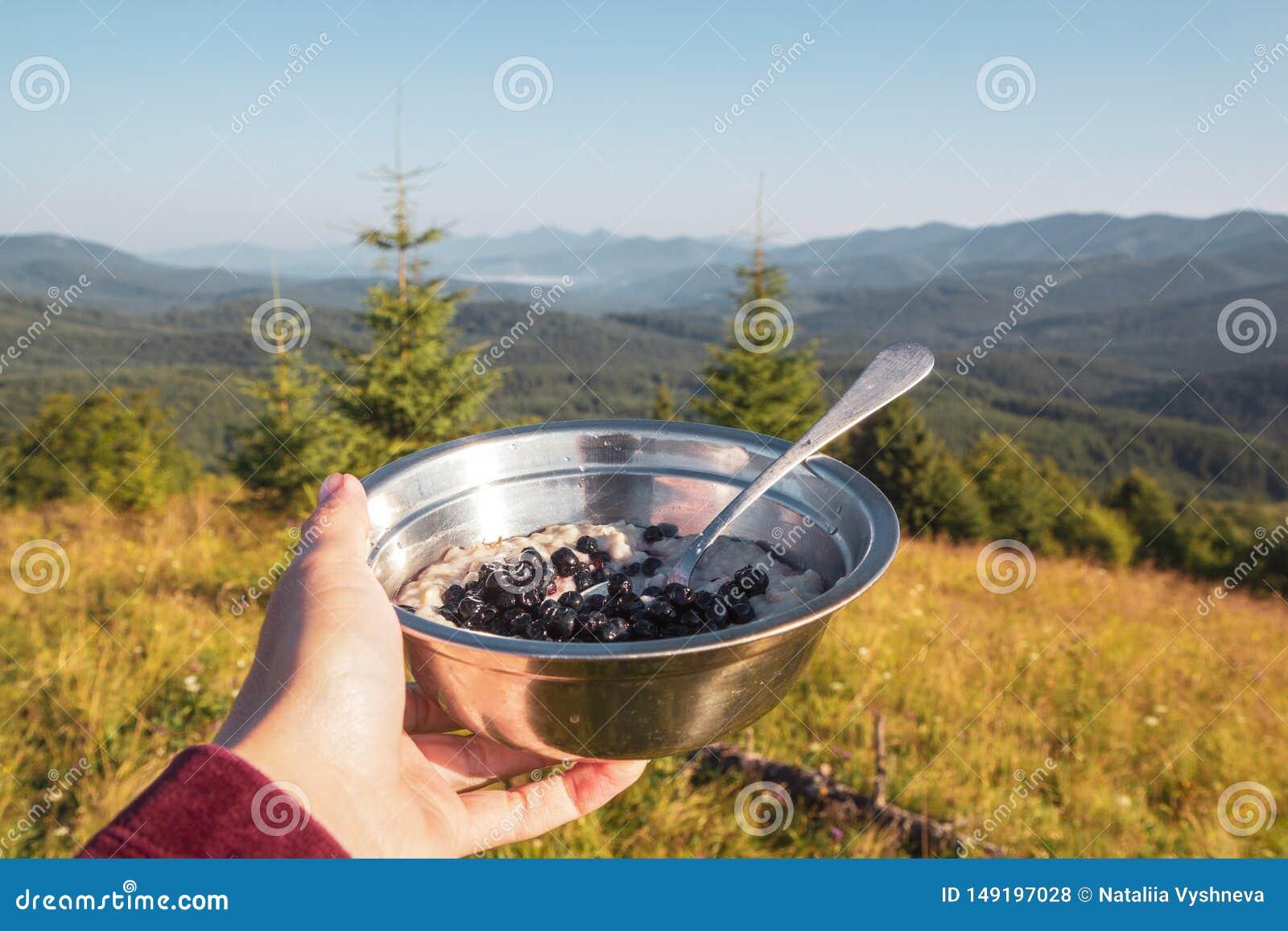 Petit d?jeuner dans la hausse, un bol de gruau et baies dans la main femelle sur le fond du paysage de montagne de matin
