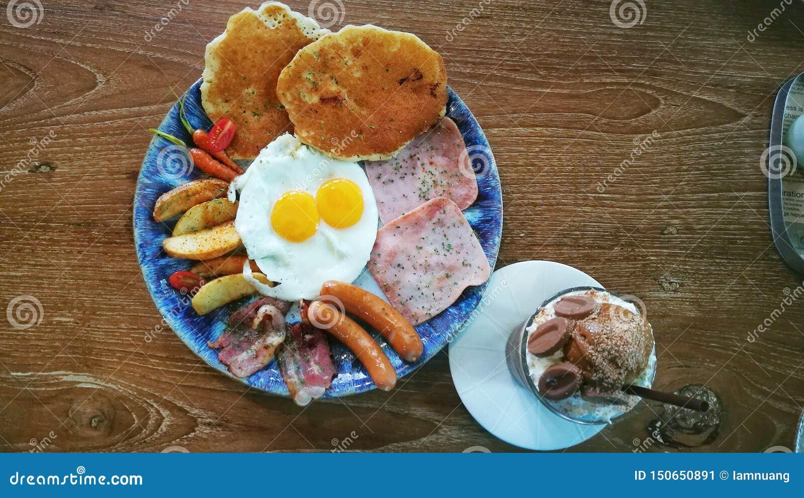 Petit déjeuner de fraîcheur avec les oeufs au plat, le jambon, les saucisses, le lard, les carottes de bébé, les pommes de terre