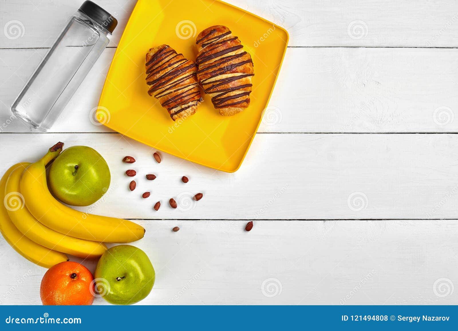 Petit déjeuner de fruit avec l espace libre sur la table en bois Croissant, banane, pomme, écrous et une bouteille de l eau Vue s