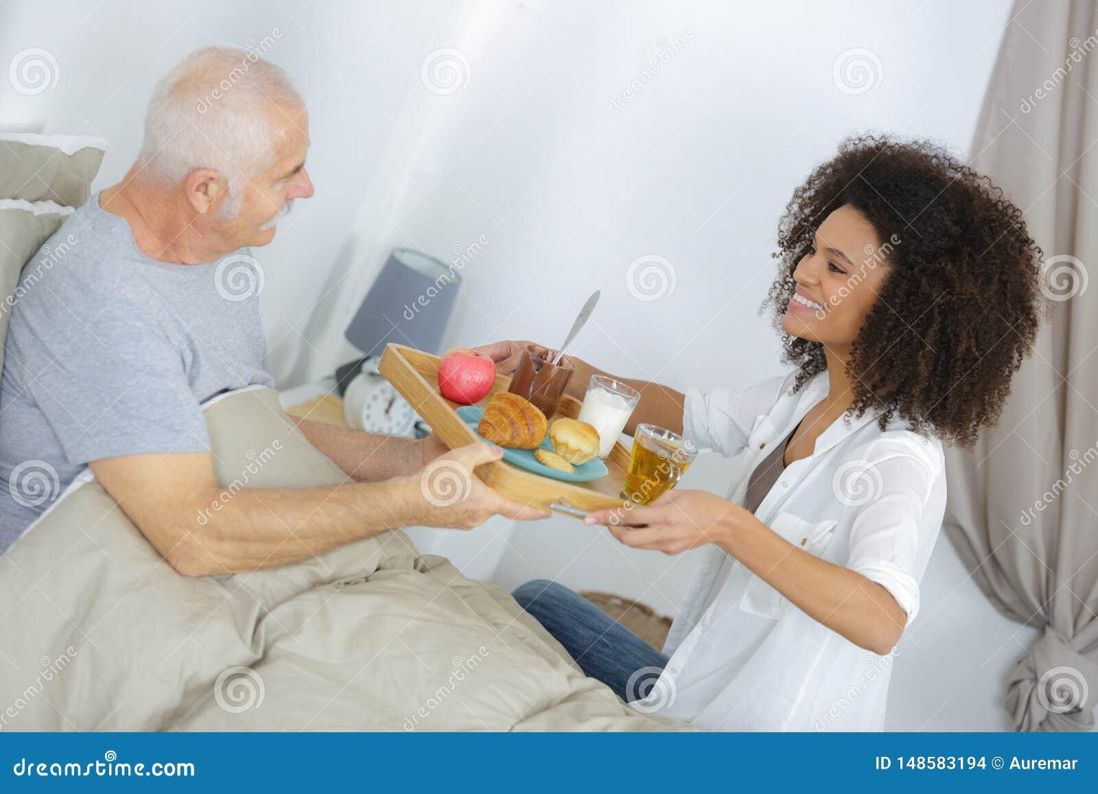 Petit d?jeuner de portion d infirmi?re ? l homme sup?rieur dans la chambre ? coucher