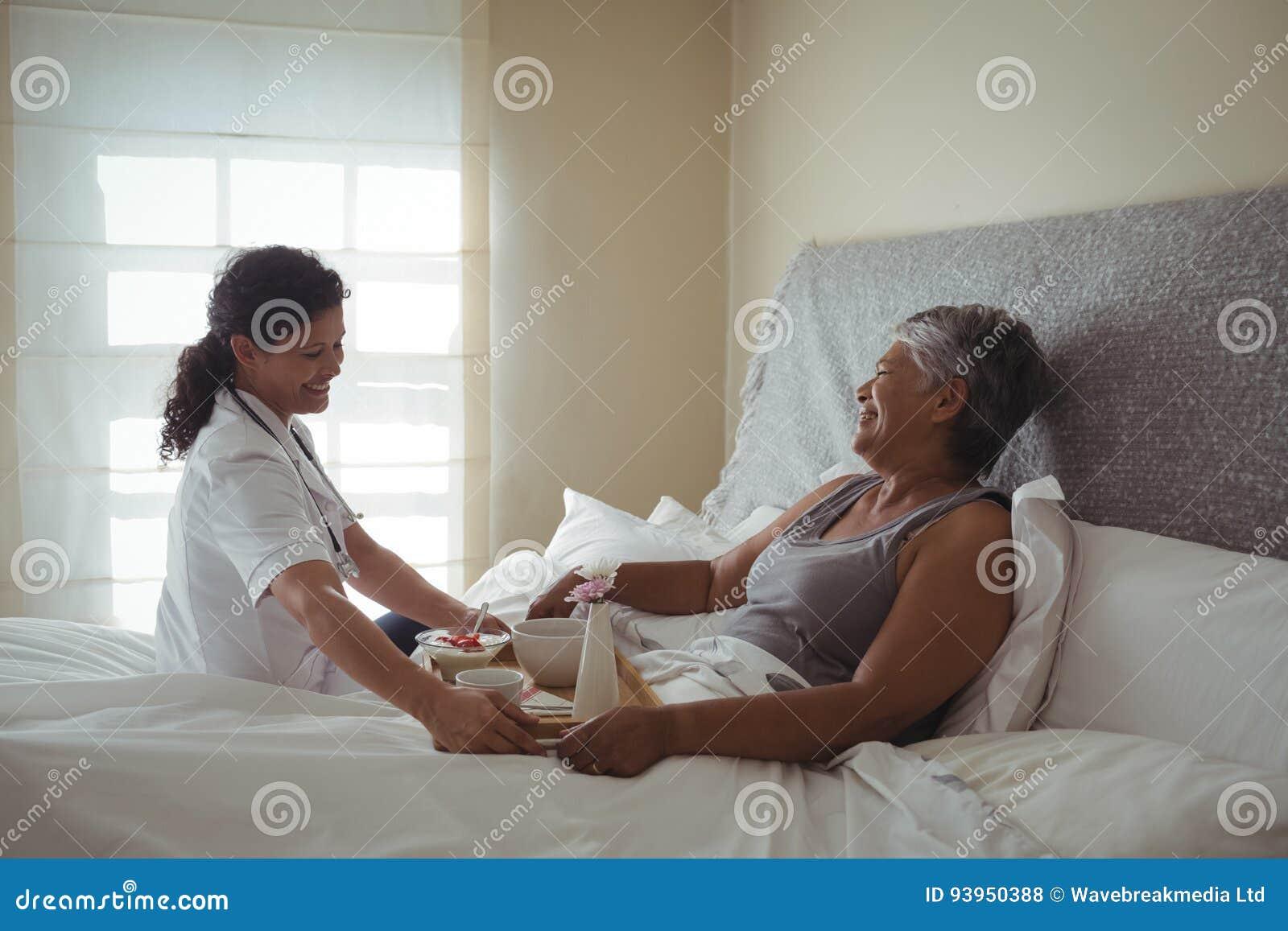 Petit déjeuner femelle de portion de docteur à la femme supérieure sur le lit
