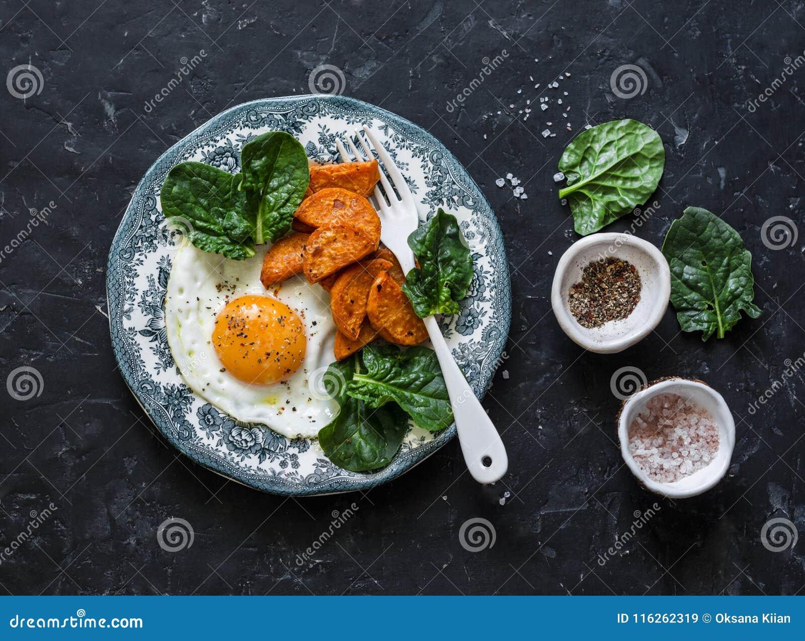 Petit déjeuner ou casse-croûte sain - oeuf au plat, patate douce cuite au four et épinards sur le fond foncé