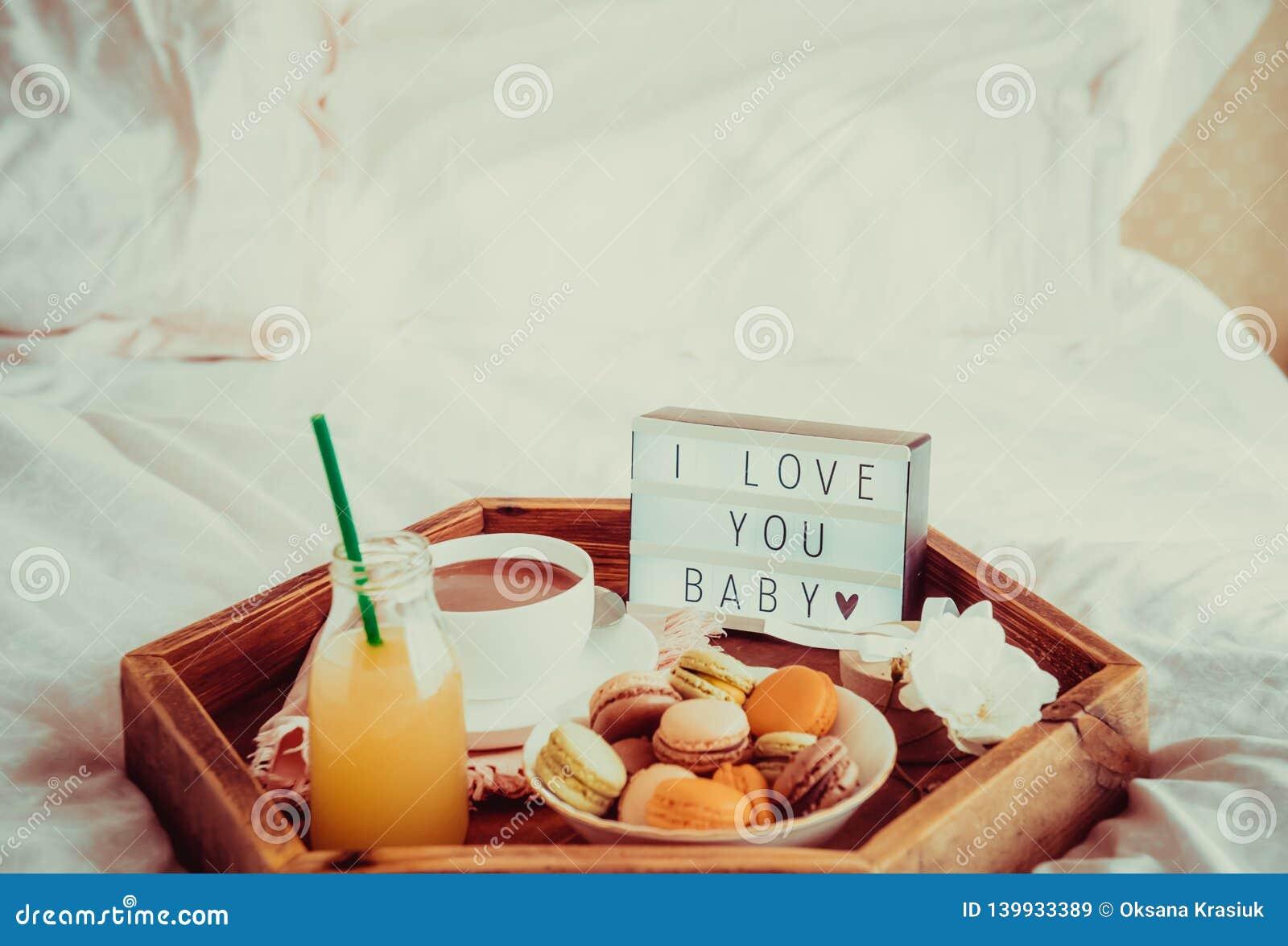 Petit déjeuner romantique dans le lit avec je t aime le texte de bébé sur la boîte allumée Tasse de café, de jus, des macarons, d