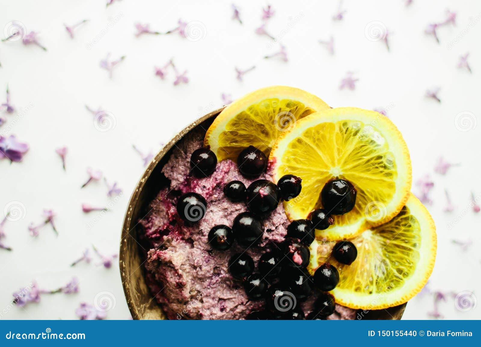 Petit d?jeuner sain de bol de smoothie dans un pot en verre avec les fleurs lilas