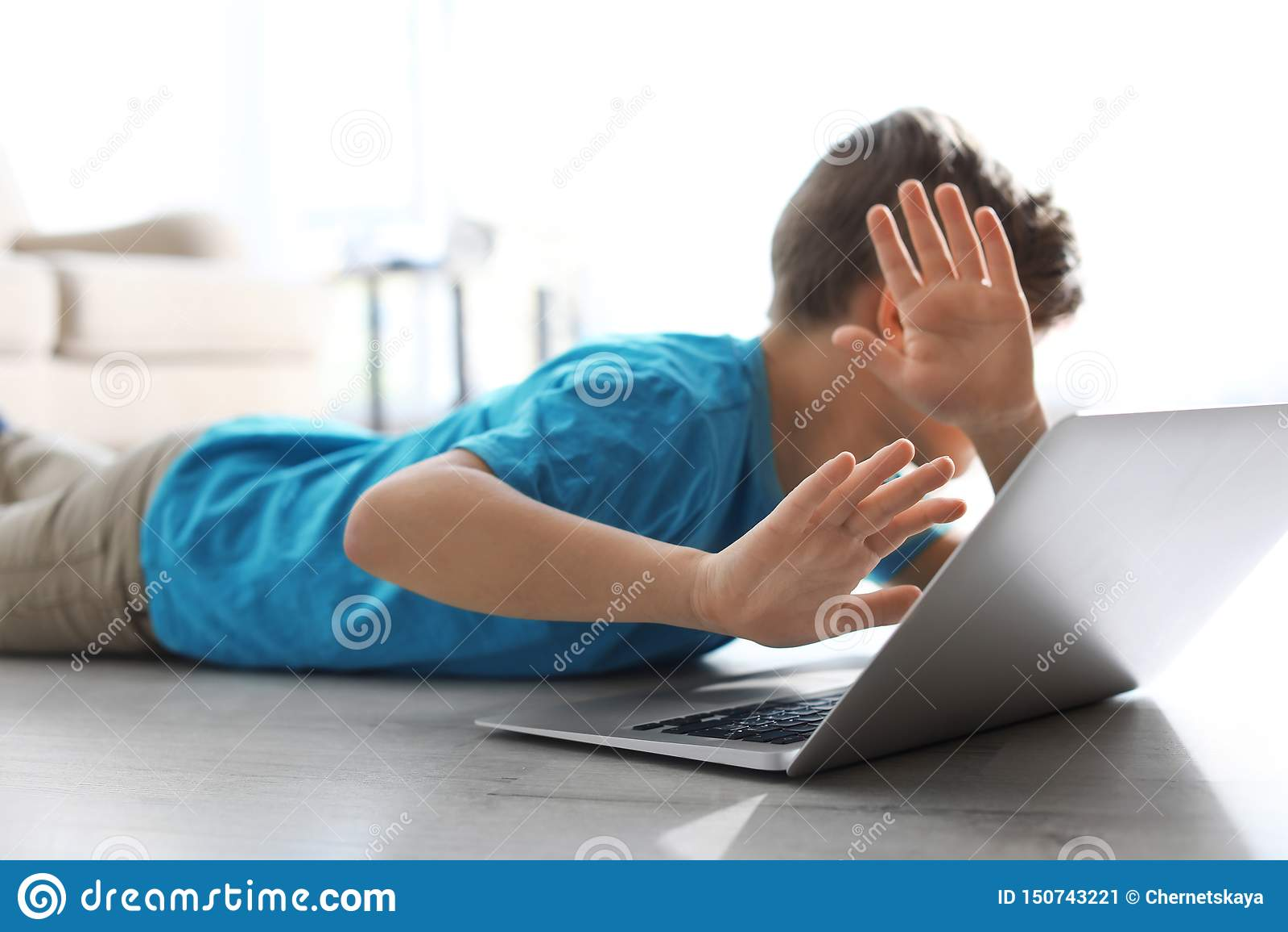 Petit enfant effrayé avec l ordinateur portable sur le plancher Danger d Internet