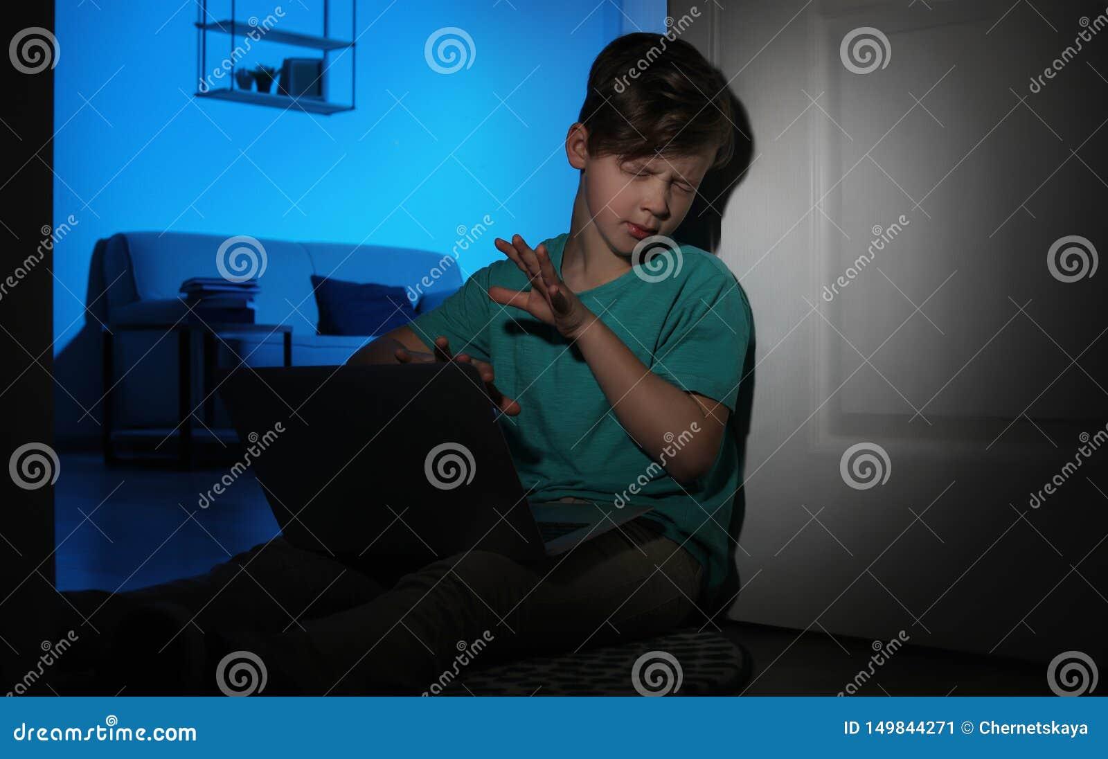 Petit enfant effrayé avec l ordinateur portable sur le plancher dans la chambre noire