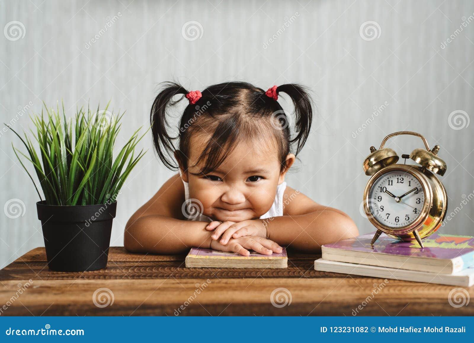 Petit enfant en bas âge asiatique mignon de bébé faisant le visage drôle ou souriant tandis que livres de lecture avec le réveil