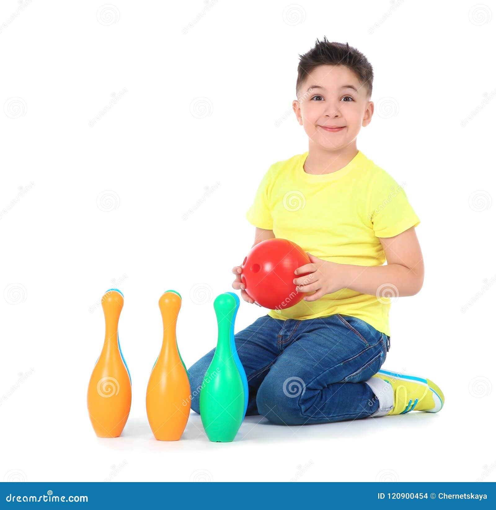 Petit enfant espiègle avec l ensemble en plastique de bowling