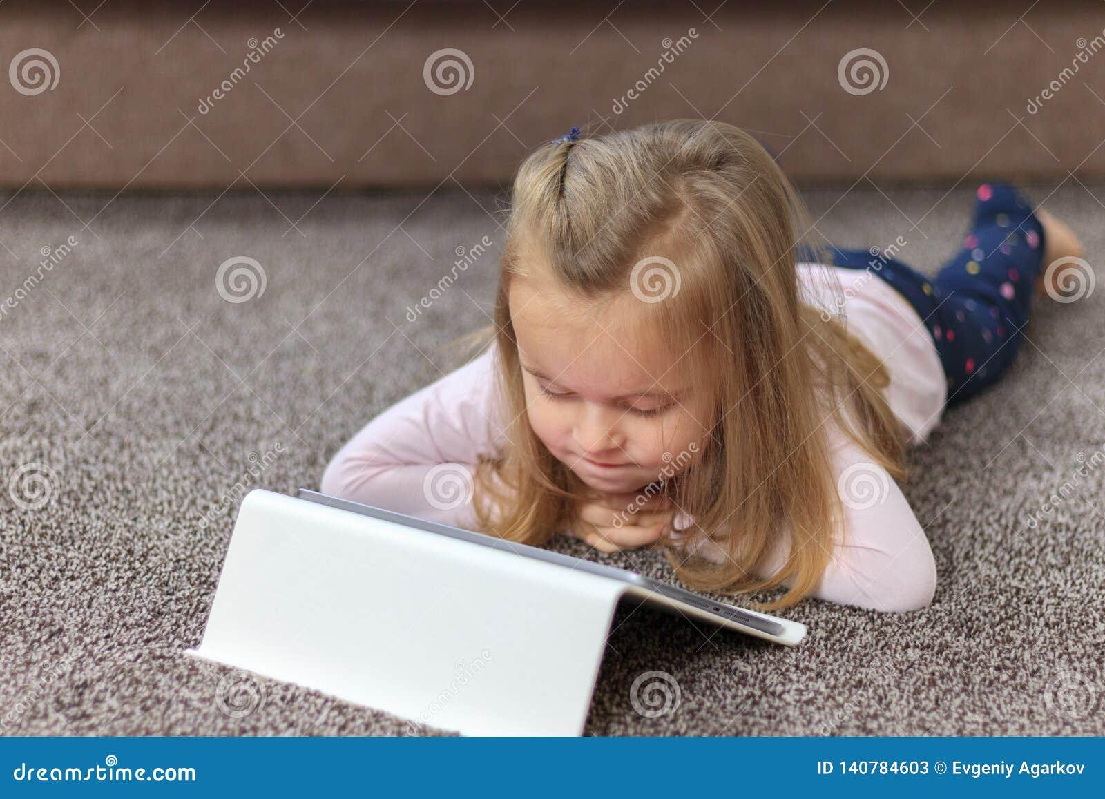Petit enfant heureux, fille blonde adorable d enfant en bas âge appréciant à l aide du PC de comprimé
