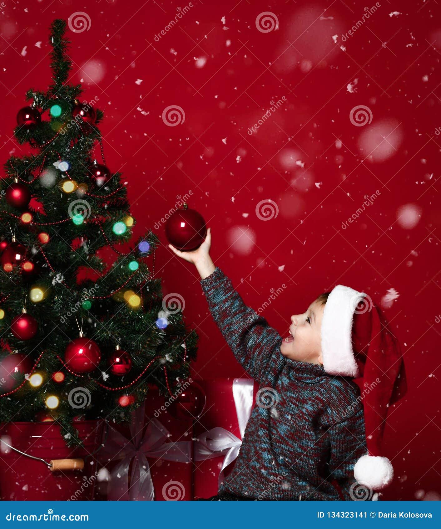 Petit enfant mignon décorant l arbre de Noël avec les perles rouges