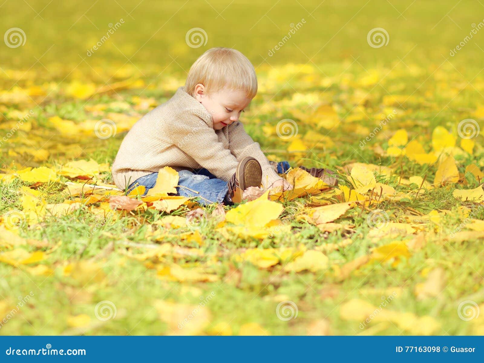 Petit enfant mignon heureux s asseyant sur l herbe et jouant avec les feuilles jaunes en automne