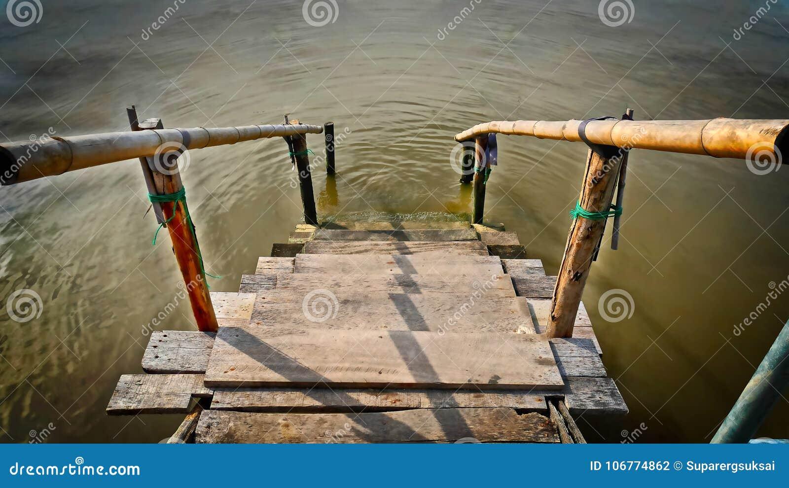 Petit Escalier En Bois De Planche Avec La Balustrade En Bambou Vers La Mer