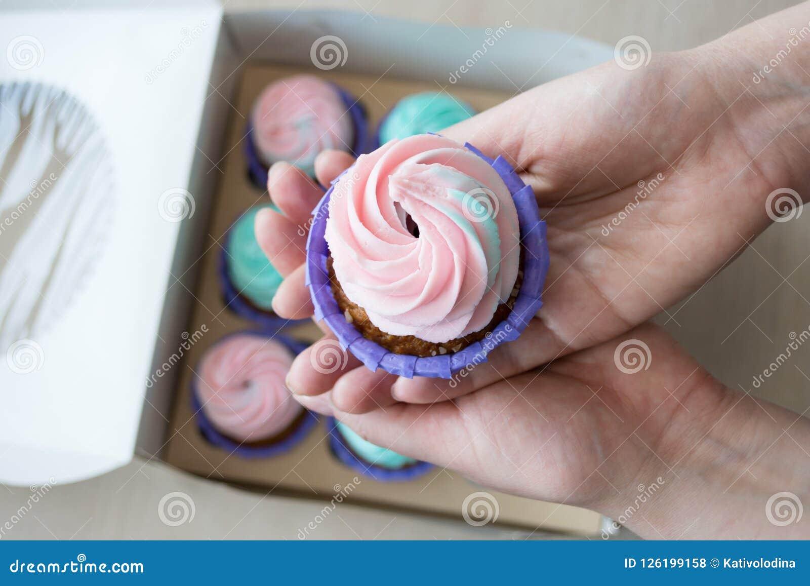 Petit gâteau avec de la crème rose et bleue dans les mains d une fille sur le fond d une boîte de petits gâteaux