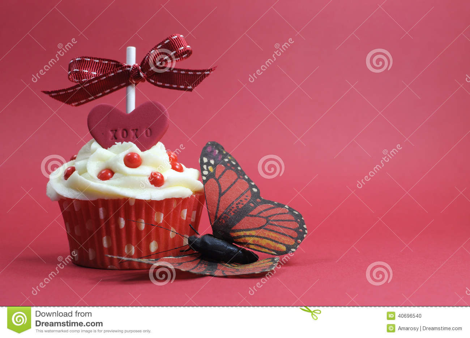 Petit gâteau rouge de thème avec le coeur d amour et papillon sur le fond rouge