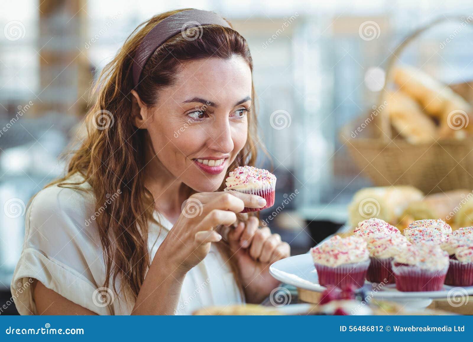 Petit gâteau se tenant et sentant de jolie brune