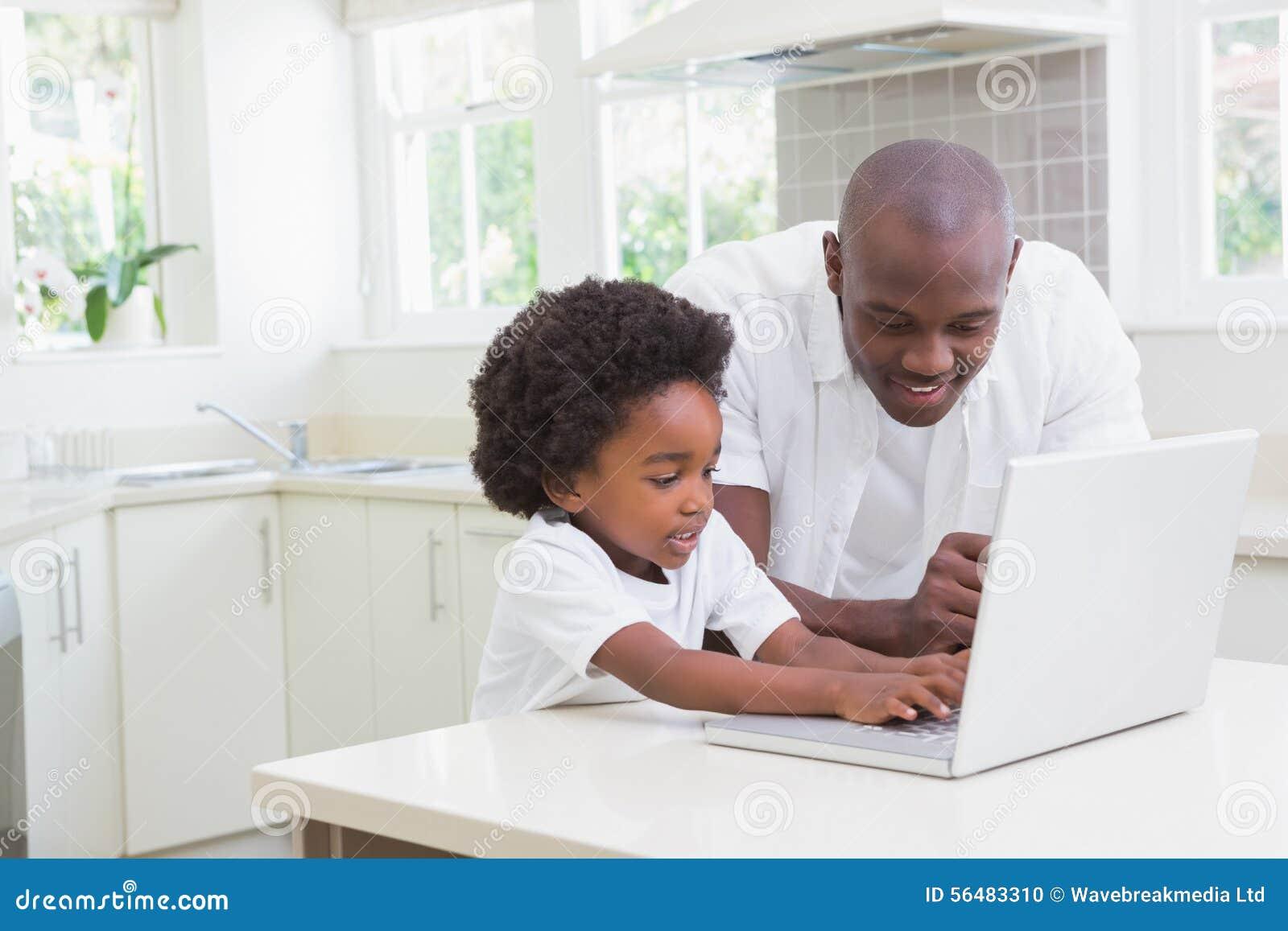 Petit garçon à l aide d un ordinateur portable avec son père