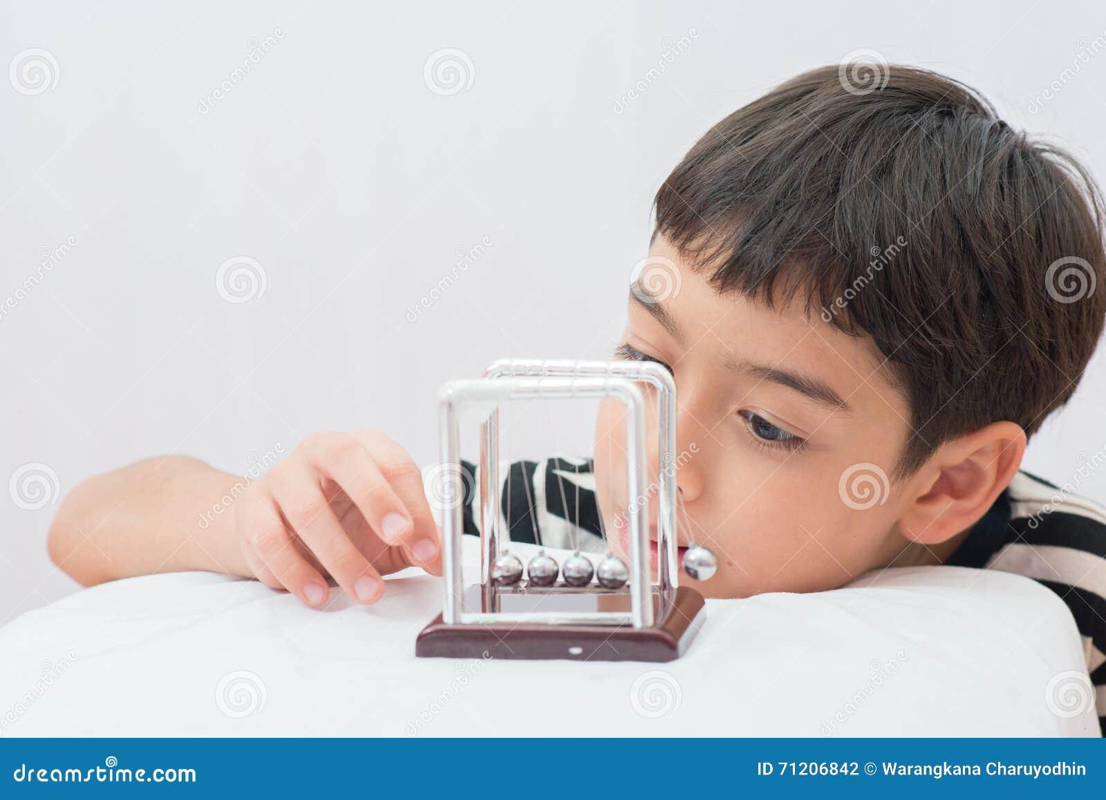 Petit garçon apprenant la boule d équilibre de newton pour le médicament de la science
