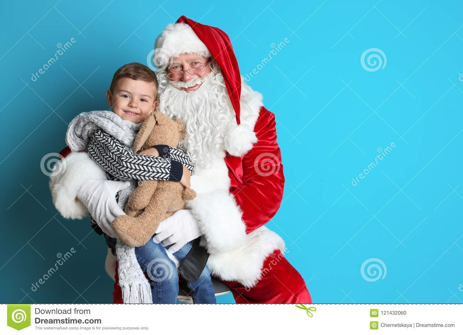 Petit garçon avec le lapin de jouet se reposant sur le recouvrement authentique de ` de Santa Claus