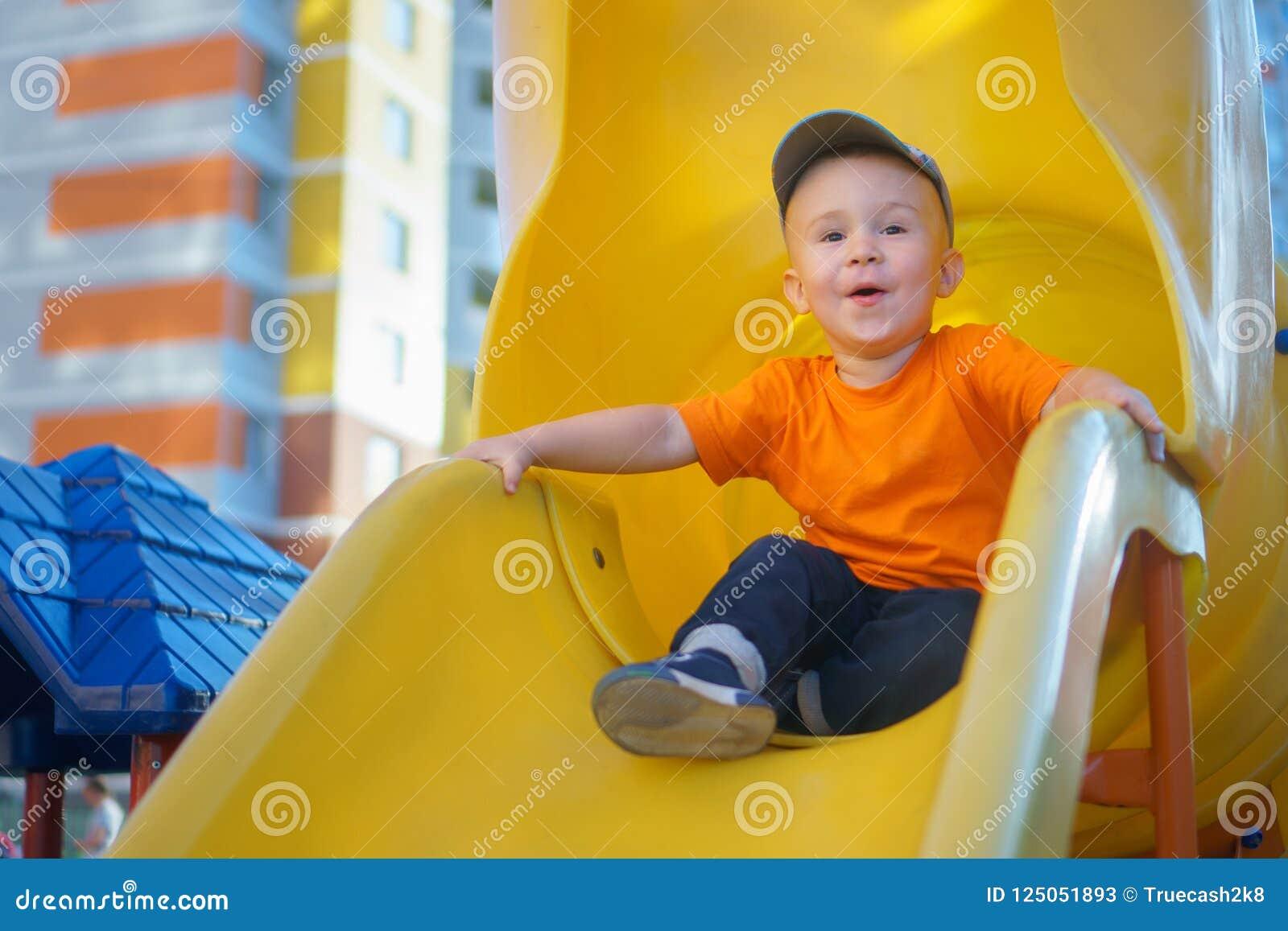 Petit garçon ayant l amusement sur un terrain de jeu dehors en été Enfant en bas âge espiègle sur une glissière
