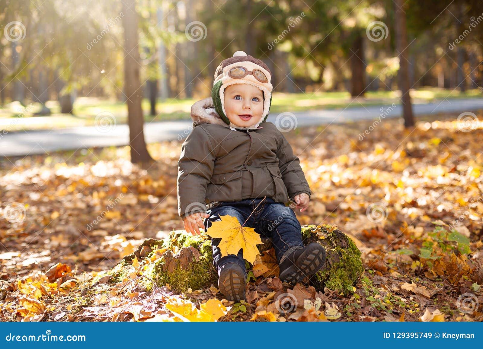 Petit garçon dans le chapeau pilote se reposant sur le feuillage de tronçon, jaune et orange autour de lui Automne