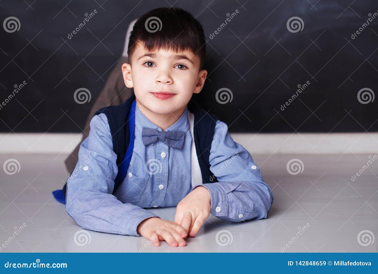 Petit garçon de sourire dans la chemise bleue regardant la caméra à la maison