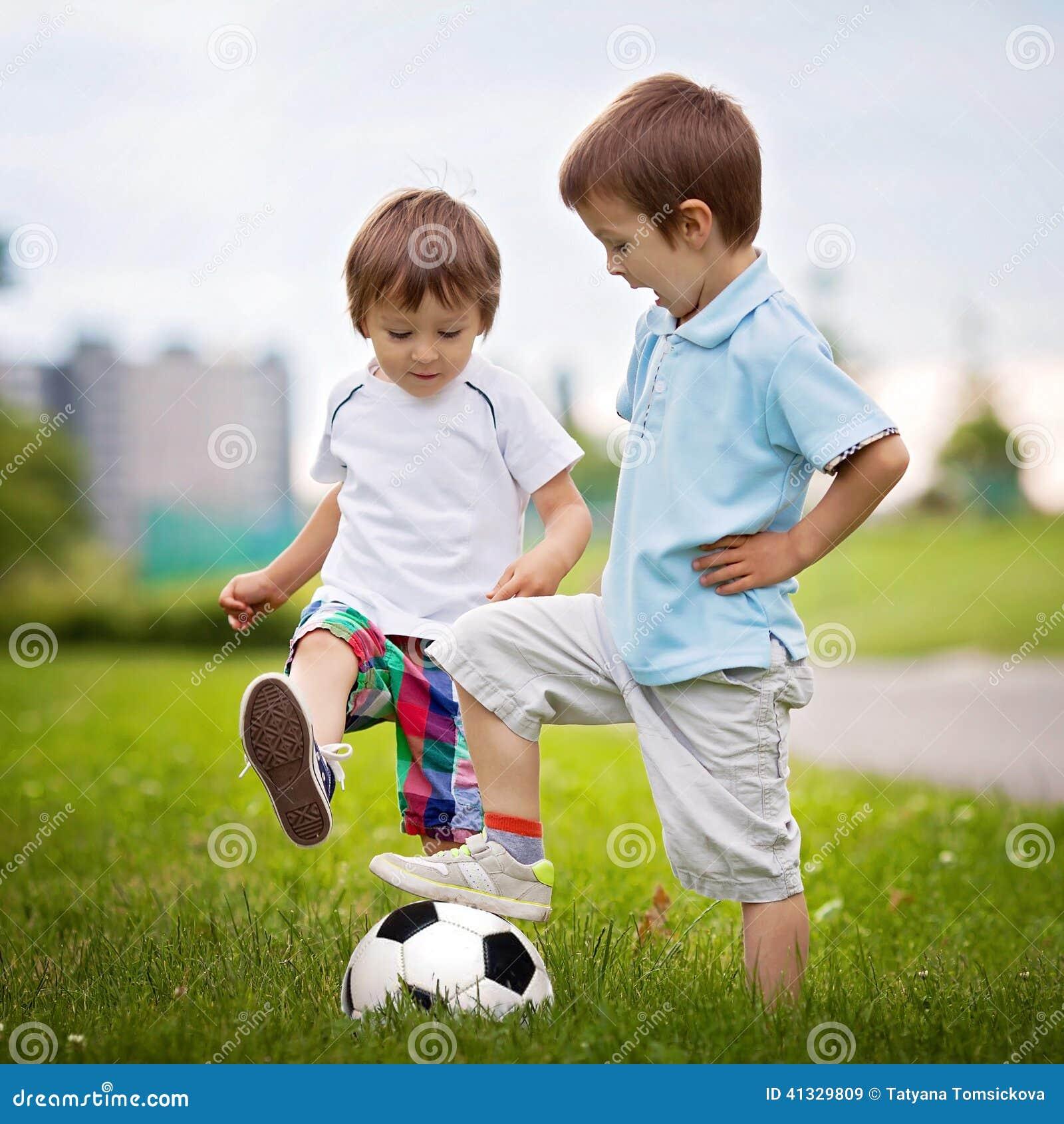 petit gar on deux jouant le football image stock image du football chaussettes 41329809. Black Bedroom Furniture Sets. Home Design Ideas