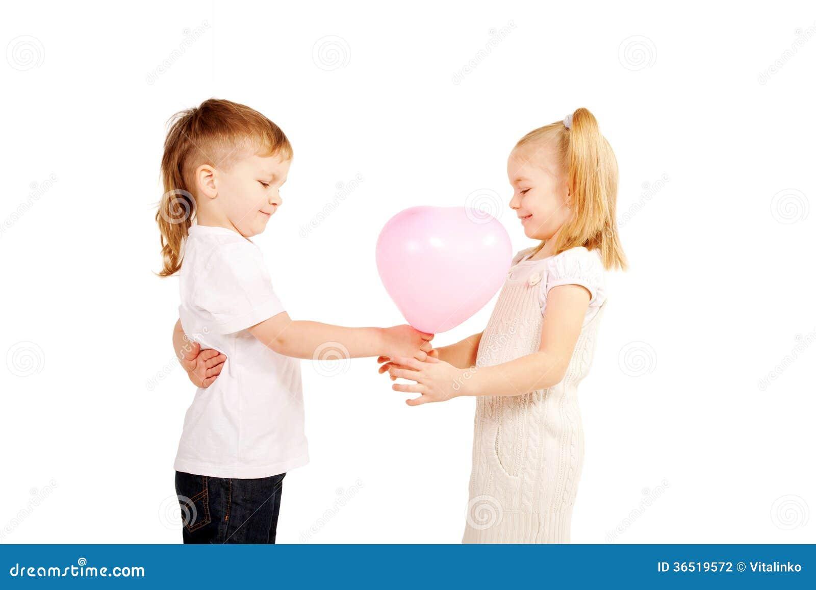 Petit garçon donnant à fille un coeur, concept du jour de valentine.