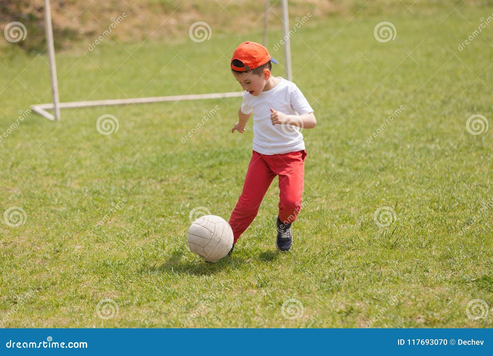 Petit garçon donnant un coup de pied la boule en parc jouer le football du football en parc sports pour l exercice et l activité