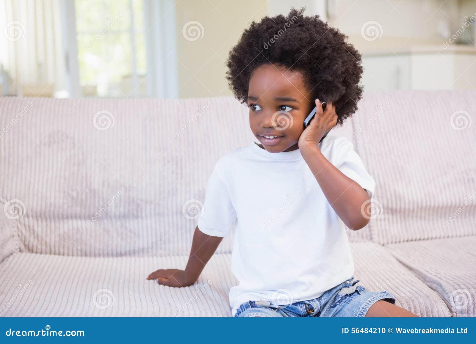 Petit garçon employant une technologie et téléphoner
