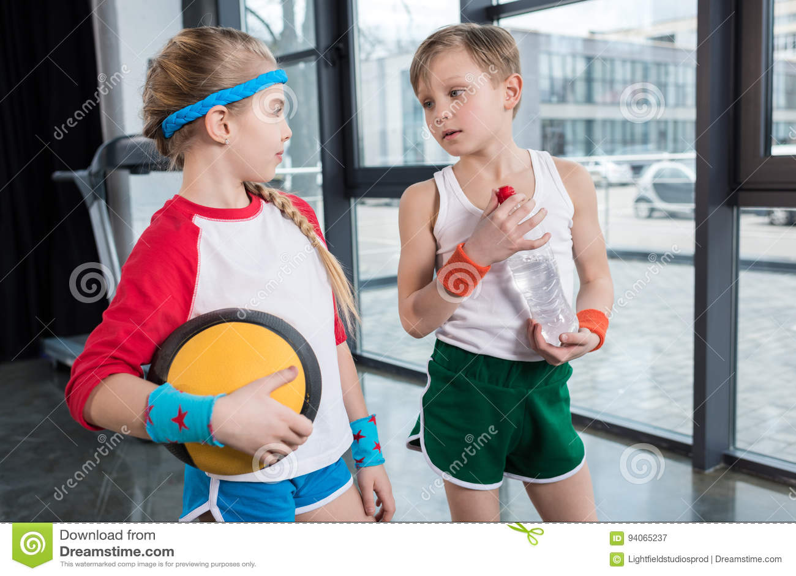Petit garçon et fille dans les vêtements de sport parlant au studio de forme physique