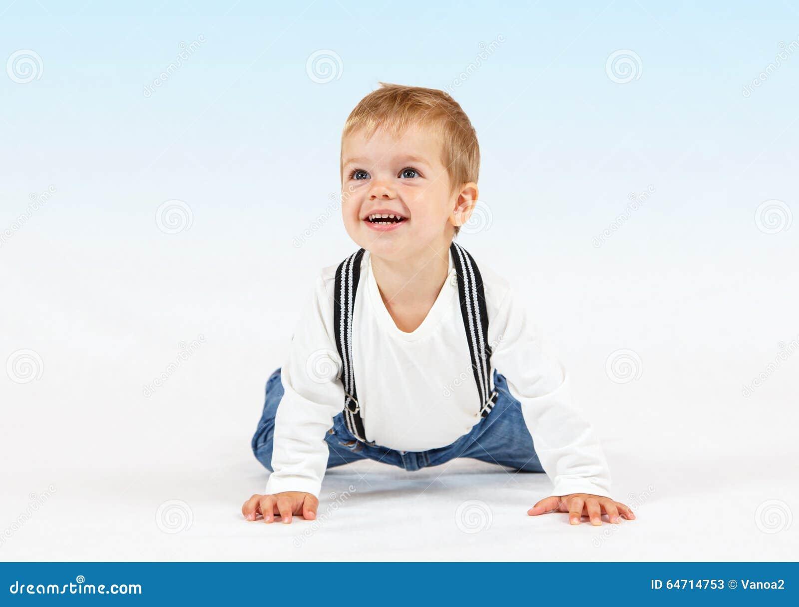 Petit garçon heureux sur le fond blanc et bleu-clair