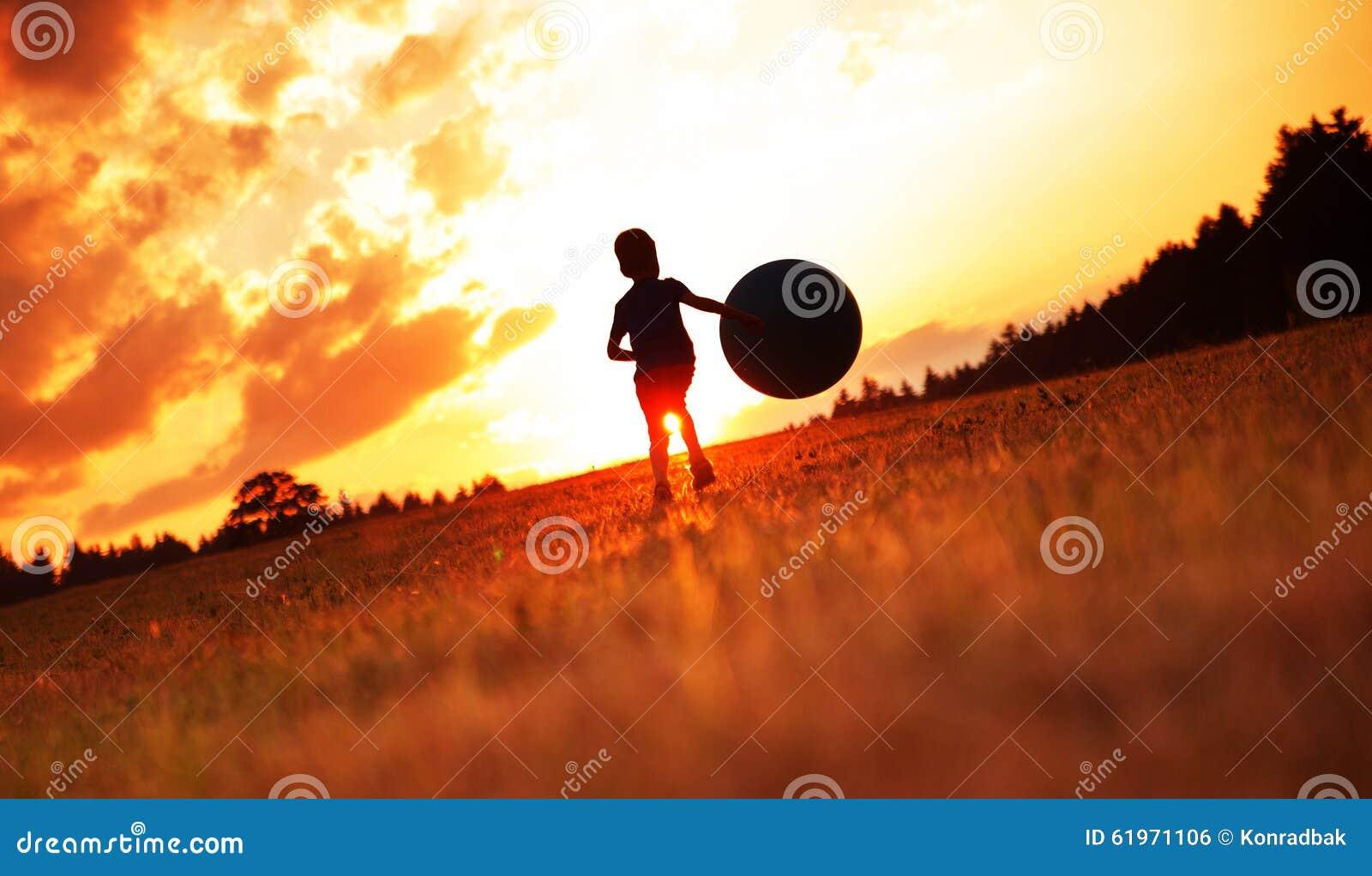 Petit garçon jouant le football sur le pré