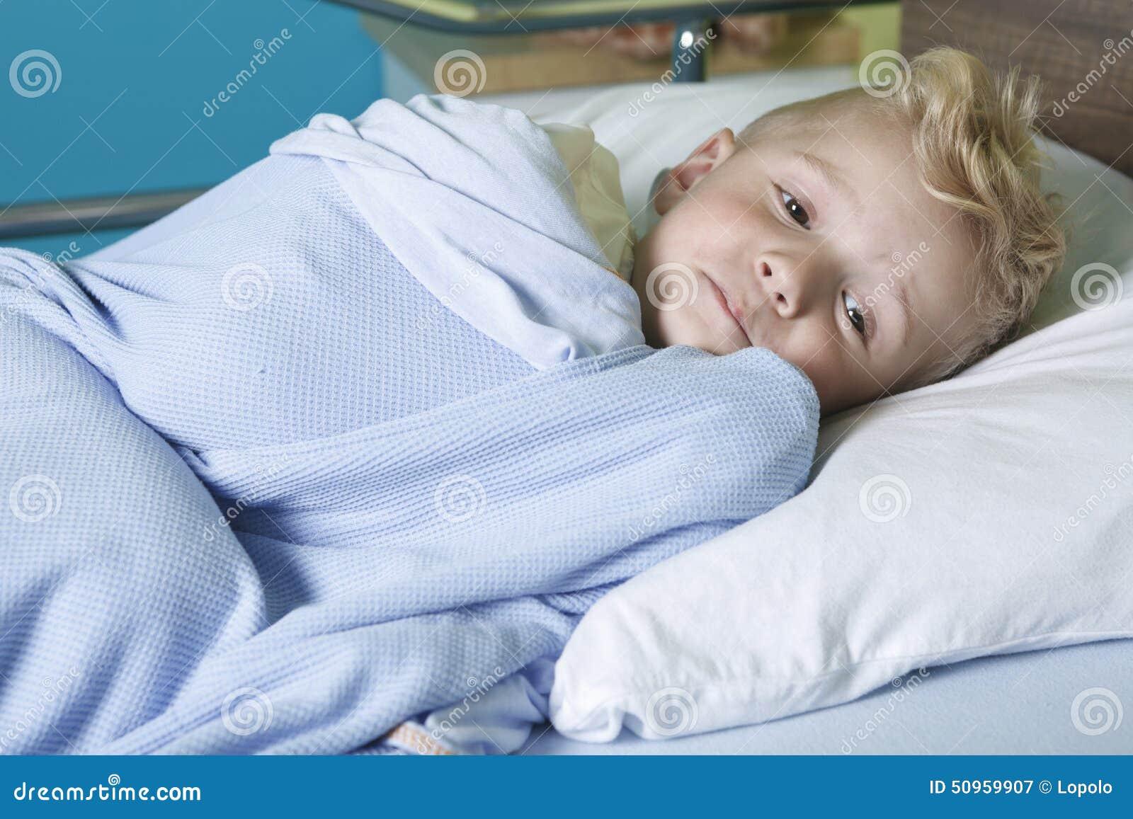 petit gar on malade dans un lit d 39 h pital photo stock. Black Bedroom Furniture Sets. Home Design Ideas
