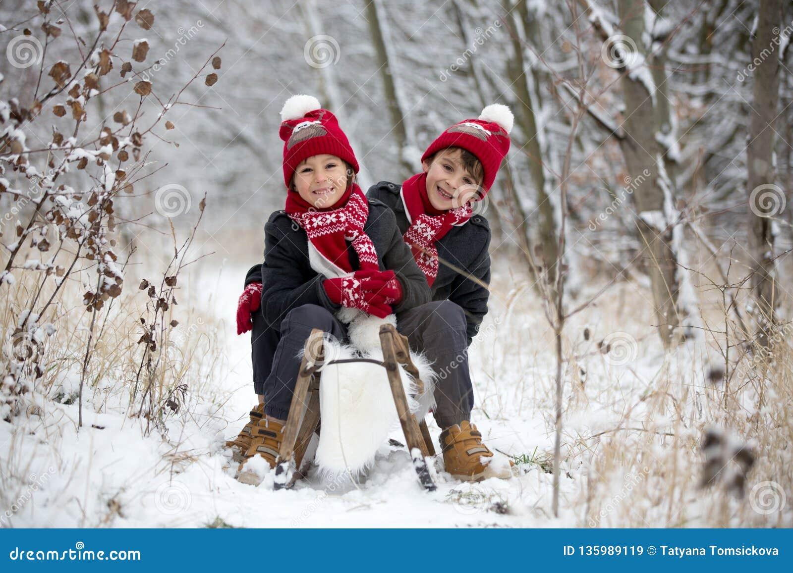 Petit garçon mignon d enfant en bas âge et ses frères plus âgés, jouant dehors avec la neige un jour d hiver