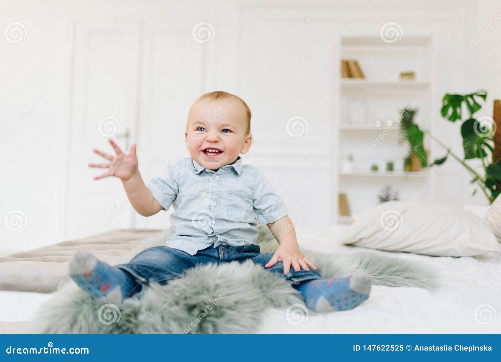 Petit garçon mignon d enfant en bas âge s asseyant sur le lit