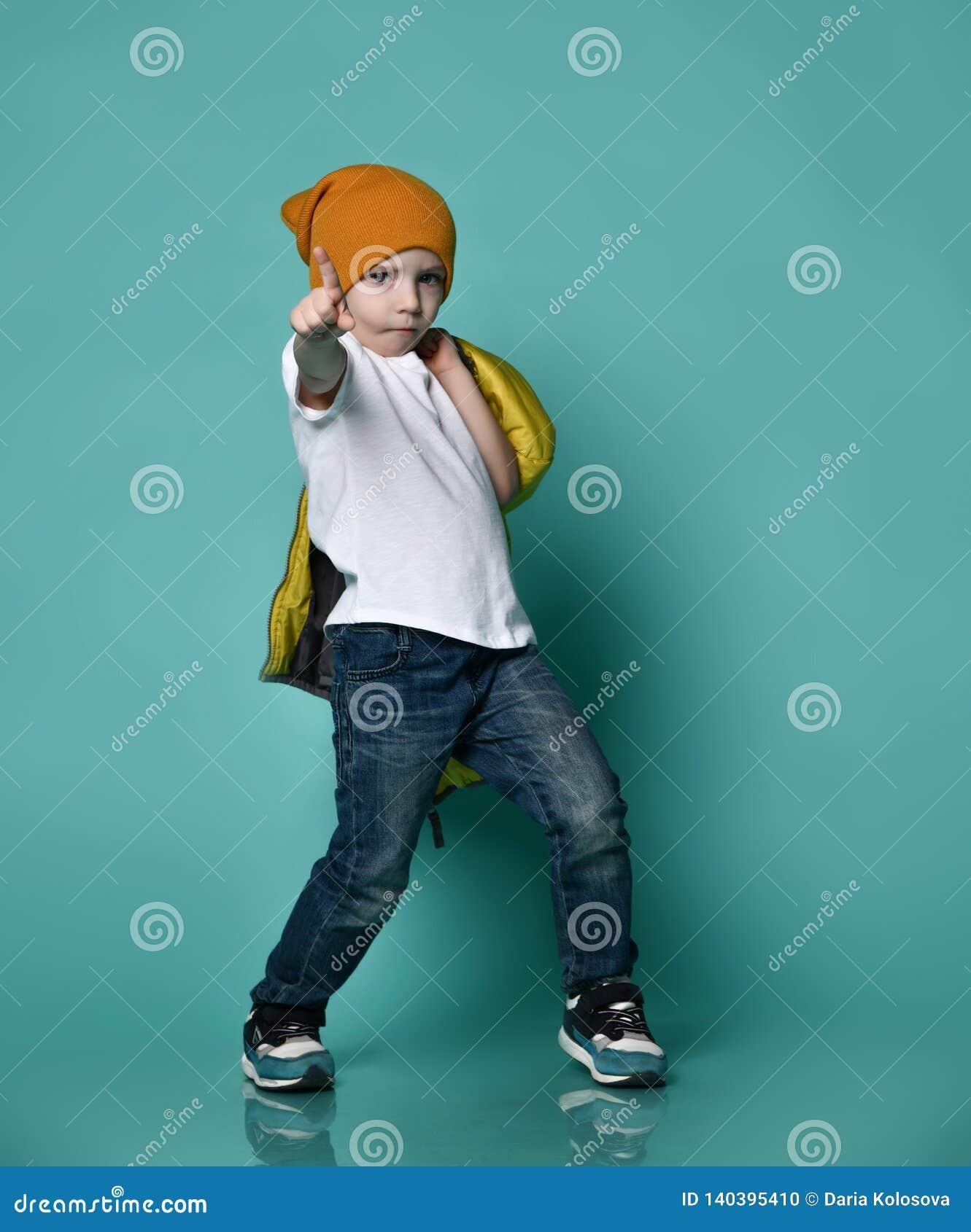 Petit garçon mignon dans le T-shirt, le chapeau et la veste blancs dans sa main posant devant le mur vert-bleu