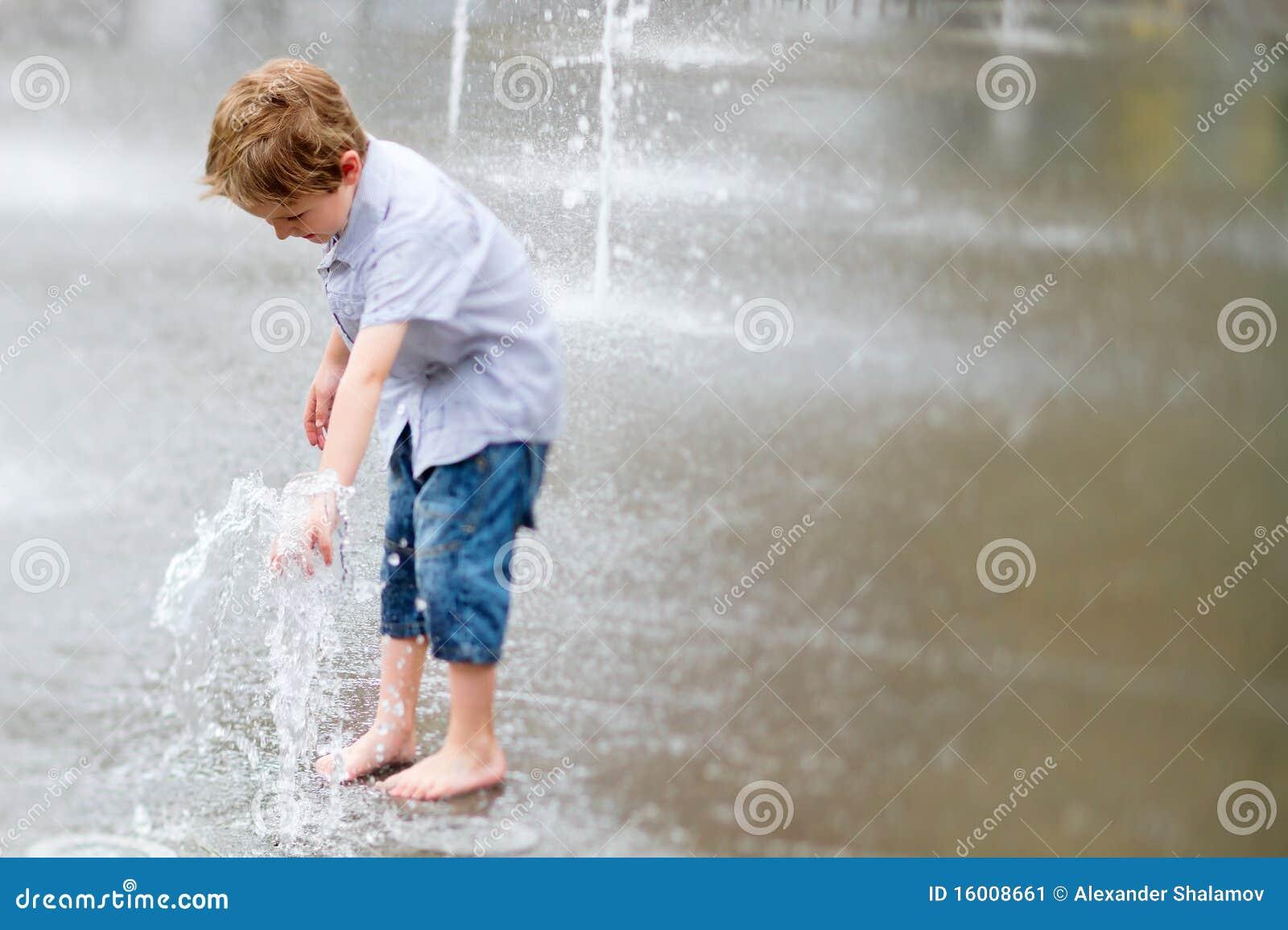 Petit garçon mignon jouant avec de l eau à l extérieur