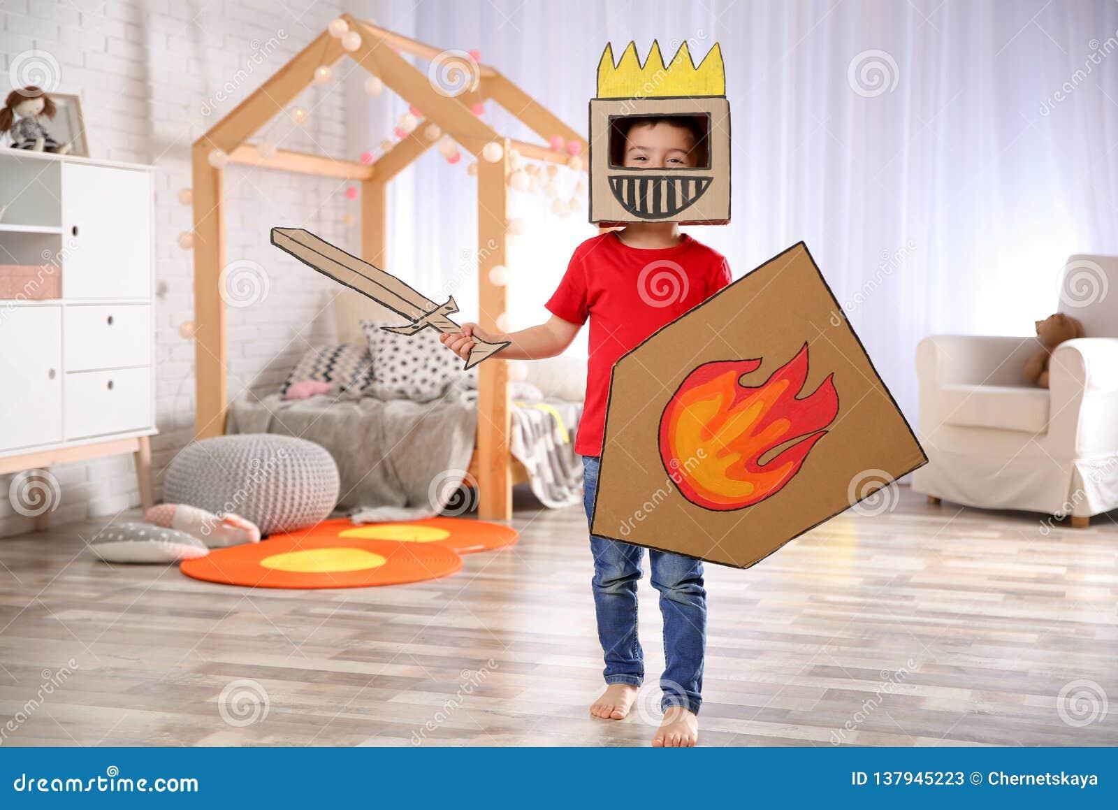 Petit garçon mignon jouant avec l armure de carton