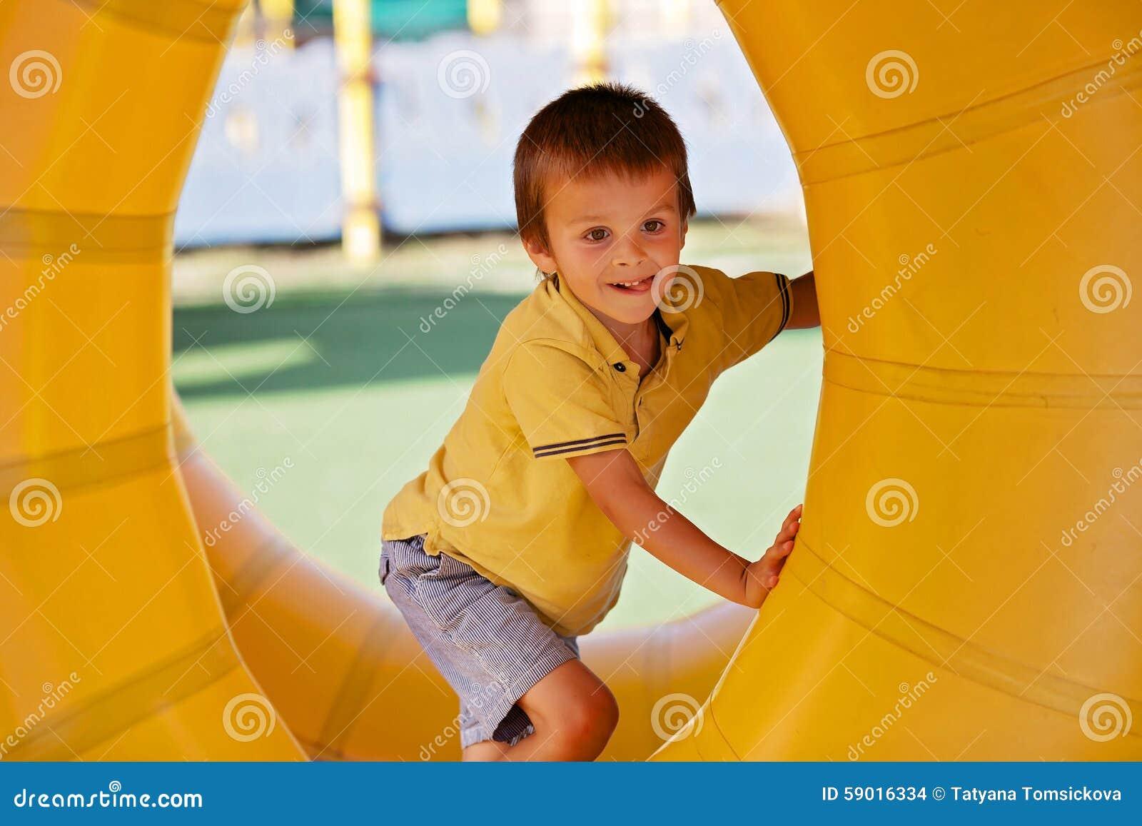 Petit garçon mignon, jouant dans un anneau en plastique de cylindre de roulement, ful